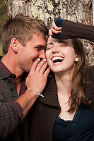 Young man wispering in woman's ear