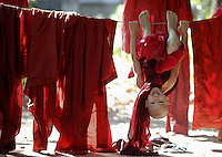 A Buddhist novice monks plays among drying robes at a monastery in central Yangon December 3, 2011. Pro-democracy leader Aung San Suu Kyi welcomed on Friday renewed U.S. engagement with Myanmar, as U.S. Secretary of State Hillary Clinton wrapped up a landmark visit to a country that was ruled by the military for five decades until March this year.   REUTERS/Damir Sagolj (MYANMAR)