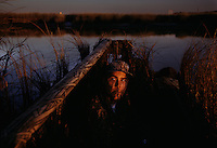Close enough to the turnpike to hear the traffic's rumble, duck hunter Mike Lawn sits in his boat equipped with cell phone and gun, waiting for birds the during opening week of hunting season.  Within one mile of this site, the Rolling Stones were warming up for a concert at the Giants Stadium--and six miles over his should loom the World Trade Center towers reflected in eveing light.