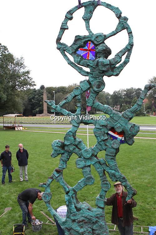 """Foto: VidiPhoto..OOSTERBEEK - Voor het Airborne Museum Hartenstein in Oosterbeek is maandag een enorm bronzen beeld van de bekende kunstenaar Jits Bakker (r) geplaatst.  Het kunstwerk, met de naam """"We'll meet again"""" is een cadeau van het Nederlandse volk aan de geallieerde 'bevrijders' die hebben deelgenomen aan de (mislukte) operatie Market Garden (1944). Het beeld staat daarom in Oosterbeek totdat er in Londen een geschikte plek voor is gevonden. Het 6 meter hoge kunstwerk is door Jits Bakker kosteloos gemaakt ter nagedachtenis aan de legendarische Slag om Arnhem en symboliseert een landende parachutist die door het uitzinnige volk wordt opgevangen als bevrijder. Bakker heeft als zevenjarig jongetje de operatie Market Garden van dichtbij meegemaakt.."""