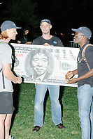 """Jason Sherfey holds a home-made $1000 bill featuring a portrait entrepreneur and Democratic presidential candidate Andrew Yang after the candidate spoke to a large crowd in Cambridge Common near Harvard Square in Cambridge, Massachusetts, on Mon., September 16, 2019. Yang's unlikely presidential bid is centered on his idea for a """"Freedom dividend,"""" which would give USD$1000 per month to every adult in the United States. After appearing in three Democratic party debates, Yang has risen in polls from longshot candidate to within the top 10. Sherfey said that the Los Angeles Yang Gang produced the Yangbucks and he just blew up the design."""