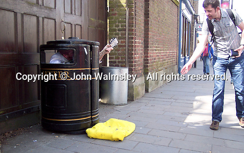 Enterprising busker inside a litter bin in Cambridge city centre.