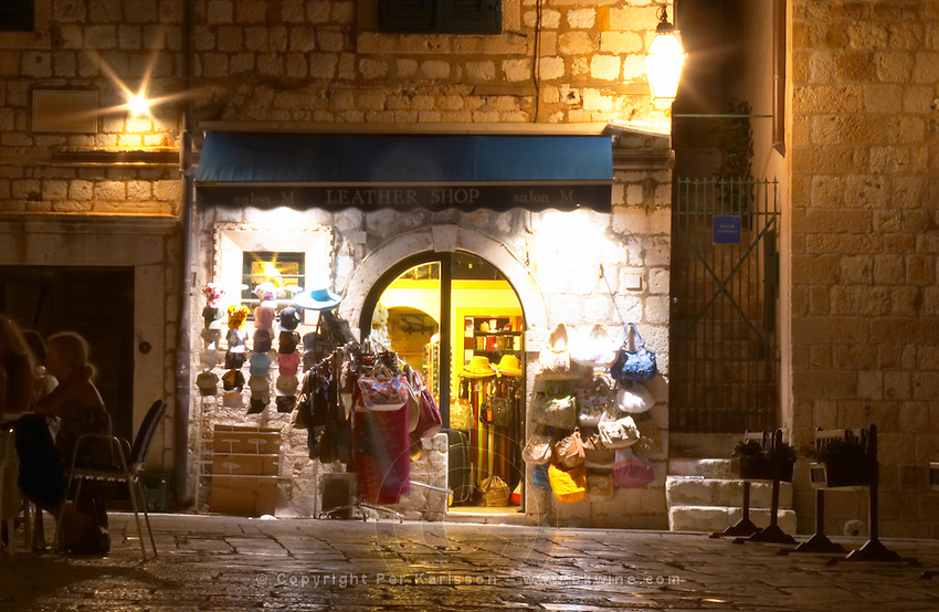 A small shop selling colourful hats and bags on the Gunduliceva Poljana square in the evening at night with street lights Dubrovnik, old city. Dalmatian Coast, Croatia, Europe.