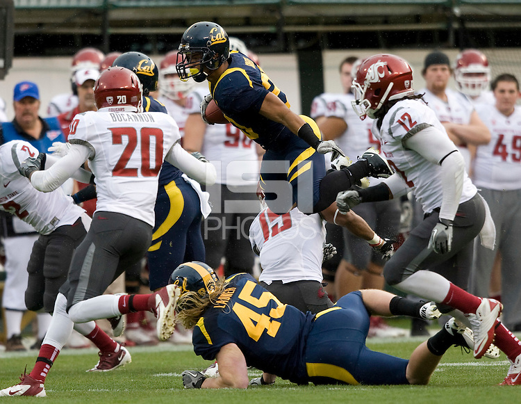 Isi Sofele of Calfornia leaps over Washington State defenders during the game at AT&T Park in San Francisco, California on November 5th, 2011.  California defeated Washington State, 30-7.