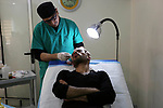 A Palestinian doctor Ahmed al-Moghrabi operates on a patient who undergo to Hair transplant surgery at his clinic, in Gaza city on February 28, 2018. Al-Moghrabi opened his clinic last year which is the first of its kind in the Gaza Strip, after years of studying in india and london and came with newest technologies to treat baldness. According to al-Moghrabi he performed about 15 surgery since he opened his clinic  each one take from 5 to 10 hours with success rate of 100%, and the surgery cost from 1000 to 1500 $ but economic situation of Gazans make the demand for this kind of surgery are very few. Photo by Ashraf Amra