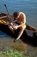 Man age 22 resting on shore of Lake Nakomis. Courage Center Canoe Race Fundraiser Minneapolis  Minnesota USA