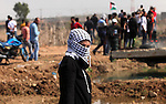 A female Palestinian protester looks on during clashes with Israeli security forces near the border fence between Israel and the Gaza Strip on October 9, 2015 east of Gaza City. Tension and protests rose after an Israeli man on 09 October stabbed four Palestinians in southern Israel, in what is being seen as a revenge attack, officials said. On 08 October several violent incidents happened, including stabbings which left eight Israelis injured, one Palestinian was killed in East Jerusalem and six in the Gaza Strip in clashes with the army while at least six were injured on the West Bank. Photo by Ashraf Amra