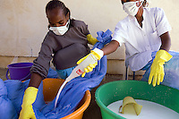 Eritrea. Hanseba province. Elaberid. Community hospital. Two black female workers, wearing a mask on the mouth and yellow gloves on both hands, are impregnating blue mosquitoes nets with permethrin, a chemical product, used to prevent people from malaria infection. The Global Fund through the eritrean Ministry of Health supports the programm with a Malaria grant (financial aid). © 2006 Didier Ruef