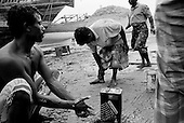 Sur, Oman<br /> July 2001<br /> <br /> Dhow boat builders clean their hands after coating a ships underbelly.