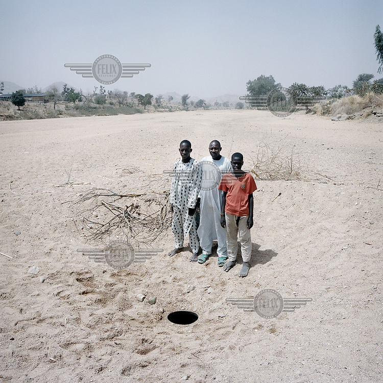 Awana Abo Boukar, 50 and his two nephews Al Hadji Dalla, 25 and Rawa, 15, collect water from a hole in a dry river bed where they have been collecting water each day for two years. The water is not safe to drink. The rainy season now arrives two months late and has exacerbated water scarcity in this area. <br /> <br /> Nigerian refugees, they left Bama in Borno state, north-east Nigeria four years ago after conflict with Boko Haram came to their village. <br /> <br /> <br /> 'I have a family of eleven, myself and my wife and nine children. We used to have four bags of rice a month to live on, now we only have two. Even if I am worried, what choice do I have? <br /> <br /> <br /> 'We left Bama in Nigeria and went by motorbike to a border town. Then we arrived here by truck. We left Nigeria because of the attacks in Bama. There were a lot of people killed. I lost my older brother. I brought all my family here.'