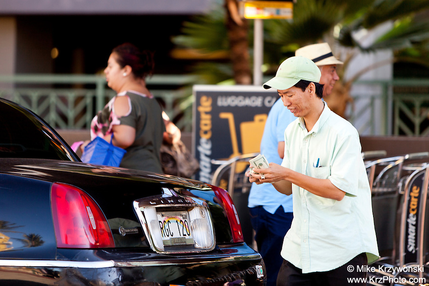 Asian taxi driver counting money at the Honolulu International Airport, Oahu, Hawaii