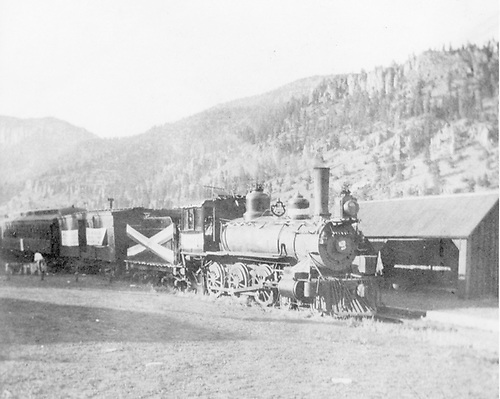 A decorated ten-wheeler locomotive with an outfit car and coach halted at an unknown location.
