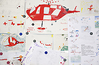 "Switzerland. Canton Ticino. Locarno Airport LSZL. The Rega base's official name is Locarno LSMO AFB (Rega 6). Drawings on the wall from children who visited the Rega base with their classes. A Rega Agusta AW109 SP Grand ""Da Vinci"" helicopter. All Rega helicopters carry a crew of three: a pilot, an emergency physician, and a paramedic who is also trained to assist the pilot for radio communication, navigation, terrain/object avoidance, and winch operations. The name Rega was created by combining letters from the name ""Swiss Air Rescue Guard"" as it was written in German (Schweizerische Rettungsflugwacht), French (Garde Aérienne Suisse de Sauvetage), and Italian (Guardia Aerea Svizzera di Soccorso). Rega is a private, non-profit air rescue service that provides emergency medical assistance in Switzerland. Rega mainly assists with mountain rescues, though it will also operate in other terrains when needed, most notably during life-threatening emergencies. As a non-profit foundation, Rega does not receive financial assistance from any government. The AgustaWestland AW109 is a lightweight, twin-engine, helicopter built by the Italian manufacturer Leonardo S.p.A. (formerly AgustaWestland, Leonardo-Finmeccanica and Finmeccanica). Leonardo S.p.A is an Italian global high-tech company and one of the key players in aerospace. In close collaboration with the manufacturer, the Da Vinci has been specially designed to cater for Rega's particular requirements as regards carrying out operations in the mountains. It optimally fulfills the high demands made of it in terms of flying characteristics, emergency medical equipment and maintenance. Safety, performance and space have been increased, and maintenance and noise emissions reduced. 20.09.2017 © 2017 Didier Ruef"