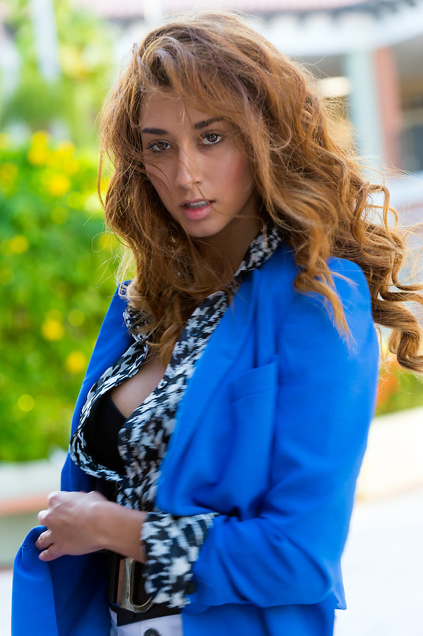 Beautiful elegant young woman dressed in trendy and stylish blouse standing outdoors looking at the camera, long curly brunette hair