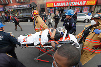 NEW YORK - FOR NEWS:  <br /> Building explosion, East 116th Street, between Madison and Park Aves, Harlem, NY Wednesday, March 12, 2014.  <br /> <br /> PICTURED:   An injured woman is taken to a waiting ambulance by rescue workers.<br /> <br /> (Angel Chevrestt, 646.314.3206)