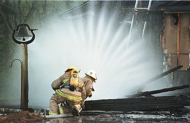 Sentinel/Dan Irving.Two firefighters use a hose to get close to a leaking natural gas line while fighting a house fire in Holland Township Wednesday, May 3, 2000.