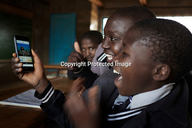 "MASERU, LESOTHO SEPTEMBER 1: A boy holds an iPhone with the ""share a meal"" app in a classroom at Masapong primary school on September 1 in Masapong district outside Maseru, Lesotho. The are given two meals a day, usually pap and fish by the World Food Program (WFP).  (Photo by: Per-Anders Pettersson)"