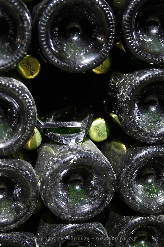 Bottles aging in the cellar. One bottle broken, exploded. Vallformosa, Vilobi, Penedes, Catalonia, Spain