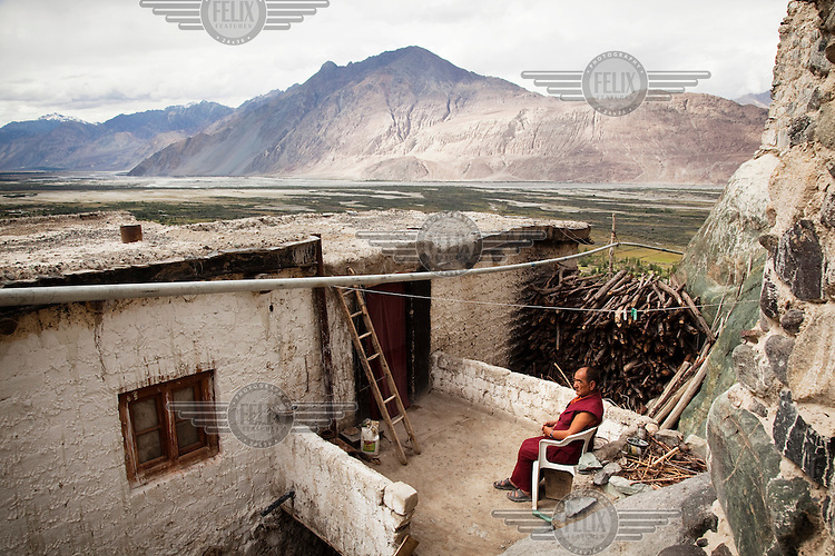 A monk sits outside his home at the Deskit or Diskit Gompa, or Buddhist monastary in the Nubra Valley. Mountains in the background.