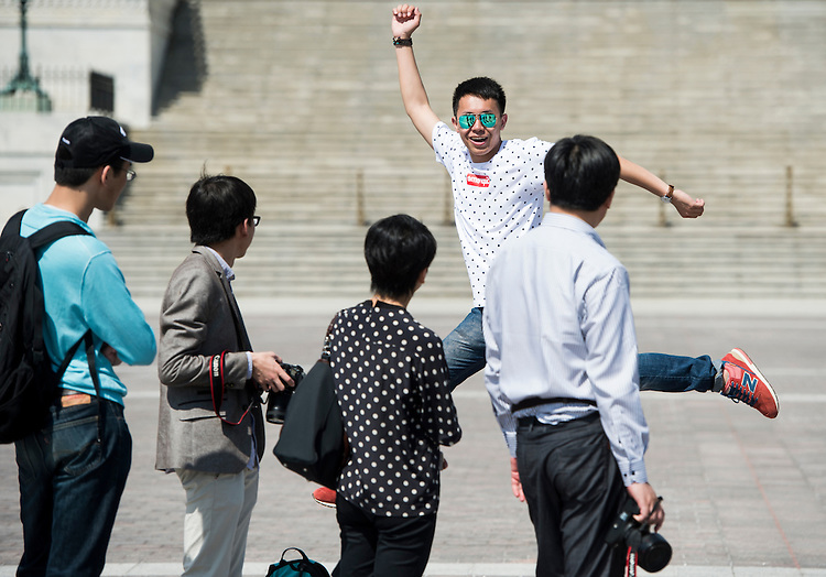 UNITED STATES - MAY 12: A tourist leaps in front of the Capitol for a photo on Monday, May 12, 2014. (Photo By Bill Clark/CQ Roll Call)