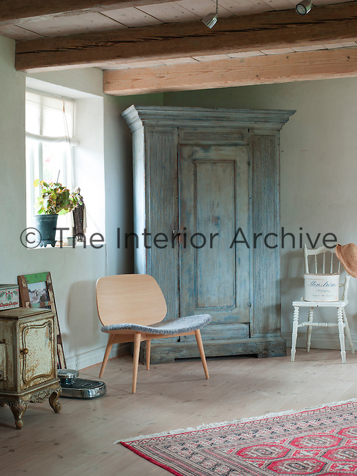 "The large blue-grey cabinet from the 1800s in the bedroom has been paired with  Jonas Lindwall's modern chair ""Papa"" with a sheepskin cushion"