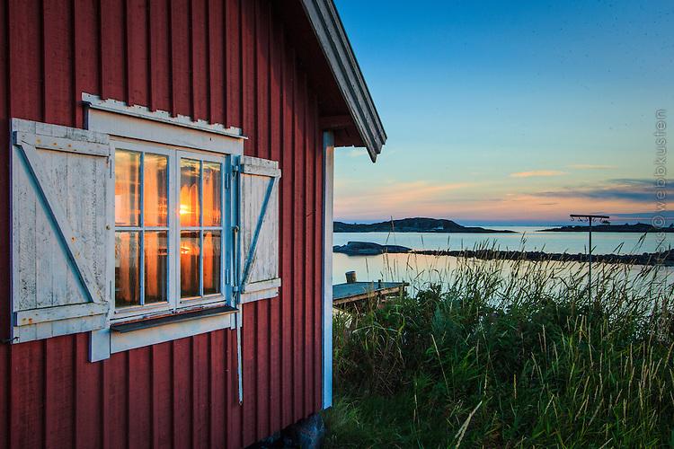 Solnedgång speglas i fönster på fiskebod å Ut-Fredel i Stockholms ytterskärgård.