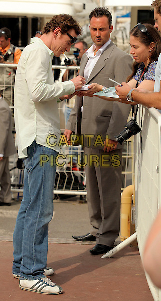 "MICHAEL FASSBENDER.""Fish Tank"" photocall at the Palais des Festivals during the 62nd International Cannes Film Festival Cannes, France. .May 14th, 2009.full length white shirt sunglasses shades profile cigarette signing autograph green.CAP/CAS.©Bob Cass/Capital Pictures."