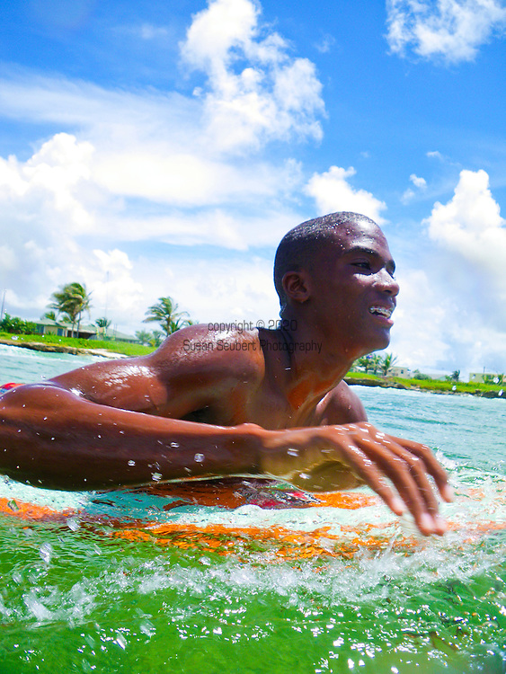 One of the young surf instructors paddling out at Zed's surf school at Surfer's Point on the South Coast of Barbados