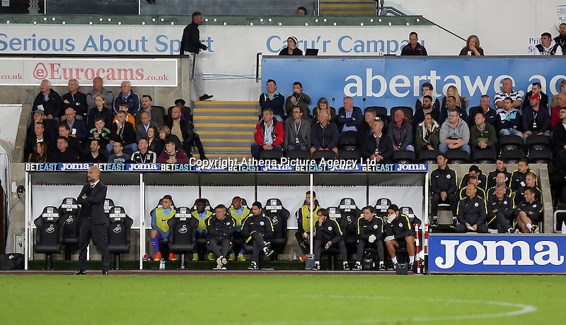 Manchester City manager Pep Guardiola with coaching staff and players in the dugout during the EFL Cup Third Round match between Swansea City and Manchester City at The Liberty Stadium in Swansea, Wales, UK. Wednesday 21 September.