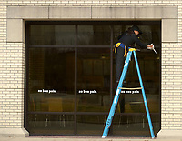 NWA Democrat-Gazette/ANDY SHUPE<br /> Cristal Hernandez, a food service worker at au bon pain, a bakery in the Arkansas Union on the University of Arkansas campus in Fayetteville, cleans exterior windows Tuesday, March 20, 2018, at the shop. With the majority of students away from campus for spring break, Hernandez said that staff were busy catching up with cleaning and maintenance.