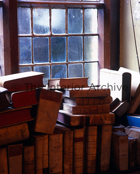 A collection of leather-bound books piled on to the window sill against a lead-paned window