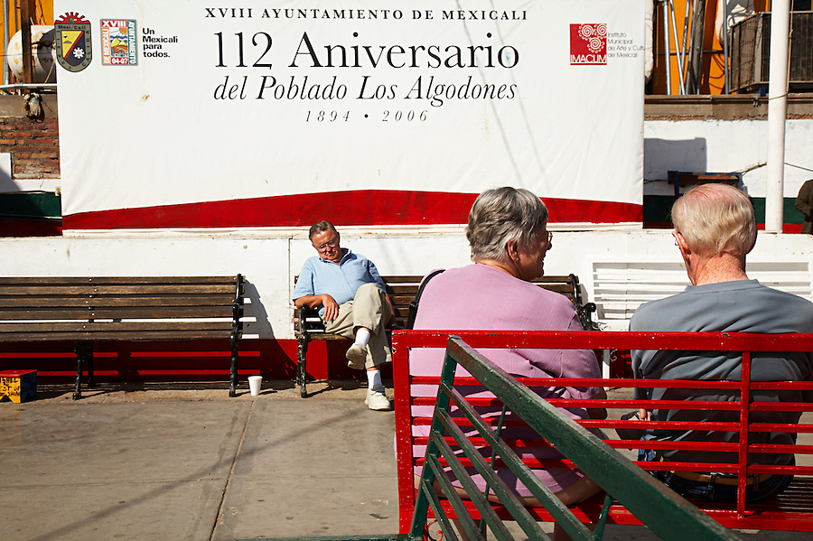Tourists relaxing on benches in the central square, Los Algodones, B.C, Mexico.
