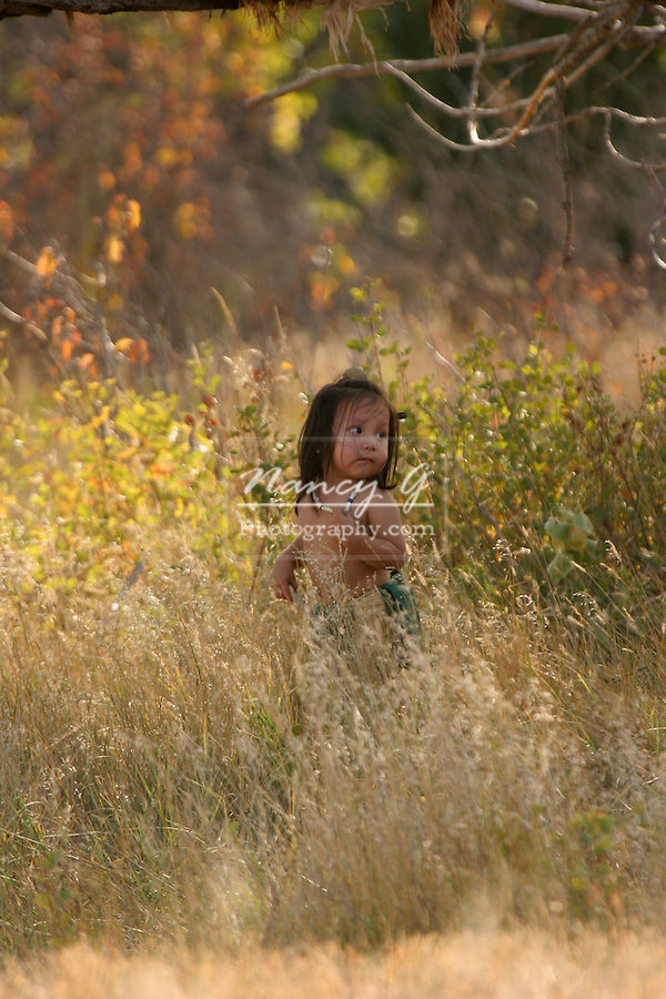 Young Native American Indian child walking in the tall grass in fall