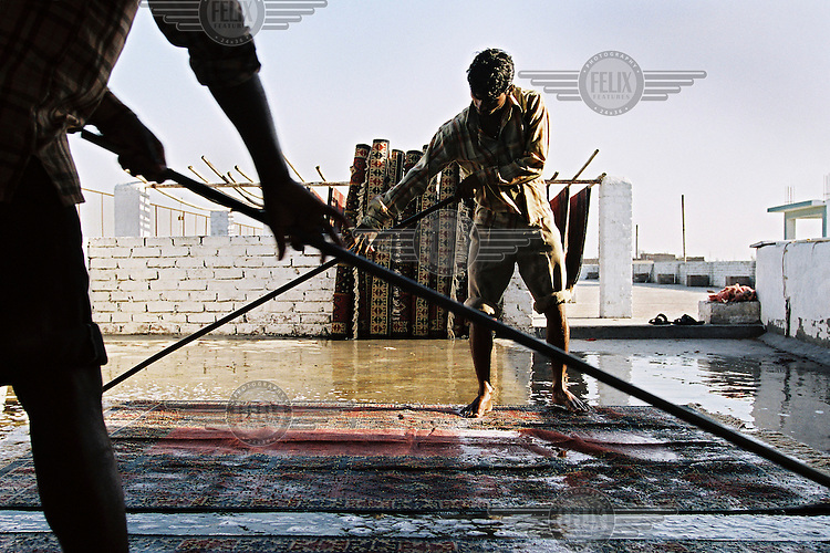 Workers finish carpets at Raj Overseas, a textiles plant on the Grand Trunk Road in Panipat. The firm manufactures a huge range of floor coverings for many household names in Britain.