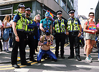 A dressed in leather outfits pose for pictures with police officers in this year's Pride Parade in the centre of Cardiff, Wales, UK. Sayurday 26 August 2017
