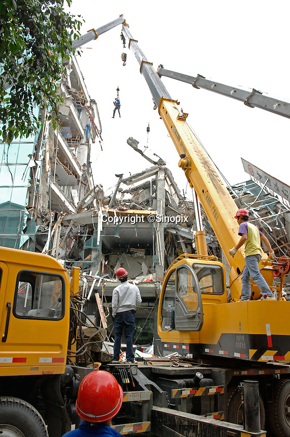 Rescue workers search the rubble of a destroyed Bank of China branch in Dujiangyan, China..14 May 2008