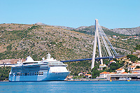 The new Dubrovnik Franjo Tudman Franja Tudmana suspension bridge at the entrance to Gruz docks harbour, Rijeka Dubrovacka bay and Kanal Daksa canal. A big luxurious cruising ship. Mountains in the background. Luka Gruz harbour. Dubrovnik, new city. Dalmatian Coast, Croatia, Europe.
