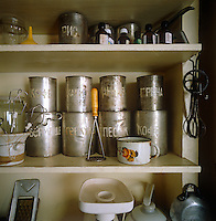 Detail of a shelf in the kitchen with its collection of original hand-painted tin canisters