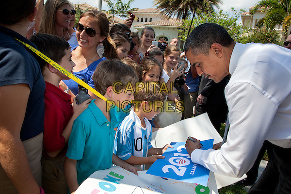 United States President Barack Obama autographs a sign while greeting neighbors and supporters before an event in Palm Beach Gardens, Florida, April 10, 2012.  .half length white shirt bending leaning side profile signing autograph kid child.CAP/ADM/PS.©Pete Souza/CNP/AdMedia/Capital Pictures.