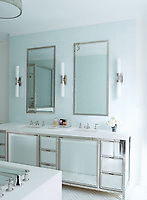 The bathroom is cool white with bespoke cabinetry. Mirrors and wall lights are placed above the double washbasins.