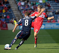 Chicago midfielder Logan Pause (12) attempts to block a clearance by New England defender Chris Tierney (8).  The Chicago Fire defeated the New England Revolution 3-2 at Toyota Park in Bridgeview, IL on Sept. 25, 2011.