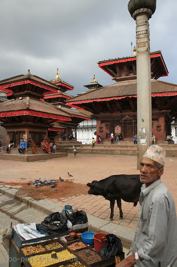 Newar street seller and cow at Durbar Square, Kathmandu, Nepal, October 2011