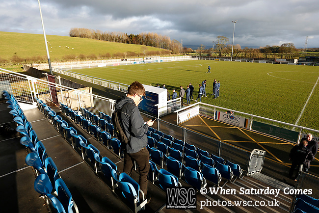An early arriver on his phone as Hebburn players inspect the pitch. Penrith AFC V Hebburn Town, Northern League Division One, 22nd December 2018. Penrith are the only Cumbrian team in the Northern League. All the other teams are based across the Pennines in the north east.<br /> Penrith, winless at kick off, lost a thriller 3-4, in front of 100 people. They won five games all season, but were reprieved from relegation following Blyth's resignation from the league.