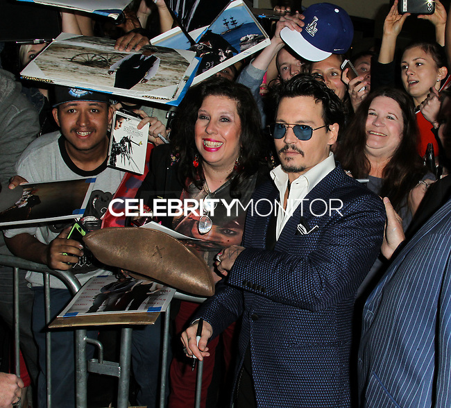 """WESTWOOD, LOS ANGELES, CA, USA - APRIL 10: Actor Johnny Depp signs autographs for fans as he arrives at the Los Angeles Premiere Of Warner Bros. Pictures And Alcon Entertainment's """"Transcendence"""" held at Regency Village Theatre on April 10, 2014 in Westwood, Los Angeles, California, United States. (Photo by Xavier Collin/Celebrity Monitor)"""