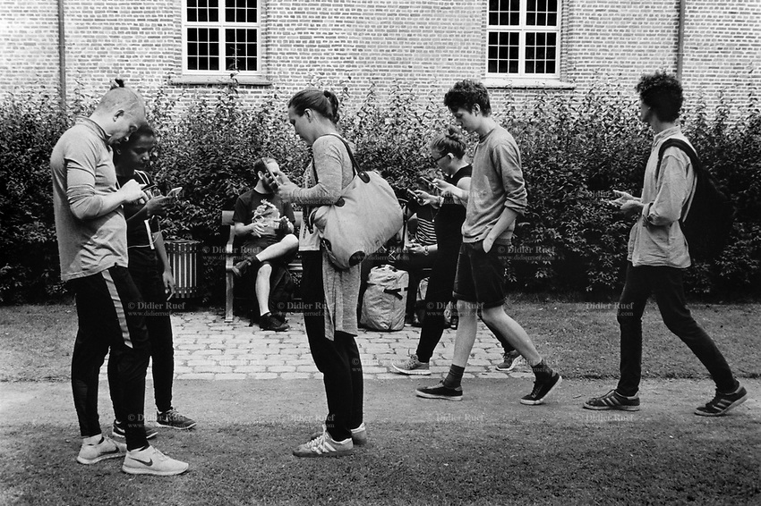 Denmark. Capital Region. Copenhagen. People play the  Pokémon Go game in the garden outside Danish Jewish Museum. Pokémon Go (stylized as Pokémon GO) is a free-to-play, location-based augmented reality game developed by Niantic for iOS, Android, and Apple Watch devices. The game is the result of a collaboration between Niantic and The Pokémon Company, and was initially released in selected countries in July 2016. In the game, players use a mobile device's GPS capability to locate, capture, battle, and train virtual creatures, called Pokémon, who appear on the screen as if they were in the same real-world location as the player. The game supports in-app purchases for additional in-game items. 6.08.2016  © 2016 Didier Ruef