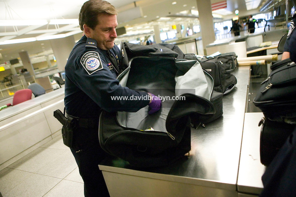 11 April 2006 - New York City, NY - CBP officer Rich Strauss checks an item of luggage not collected by passengers, known as LOBs for leftover bags, for a double lining at JFK airport in the Queens borough of New York City, USA, 11 April 2006.
