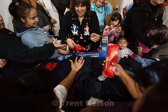 Volunteer Monica Wilson hands out gifts at the Christian Life Center. The Salt Lake City Mission planned on serving 2,000 ham and turkey suppers this year, more than ever before, at the Christian Life Center. Toys, personal care items and warm clothes were distributed all day. Friday, December 25, 2009.