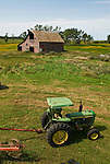 Weathered red wooden barn, John Deere 2440 tractor with rake wheel, North Dakota