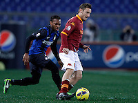 Calcio, semifinale di andata di Coppa Italia: Roma vs Inter. Roma, stadio Olimpico, 23 gennaio 2013..AS Roma forward Francesco Totti is chased by FC Inter midfielder Joel Obi, of Nigeria, left, during the Italy Cup football semifinal first half match between AS Roma and FC Inter at Rome's Olympic stadium, 23 January 2013..UPDATE IMAGES PRESS/Isabella Bonotto