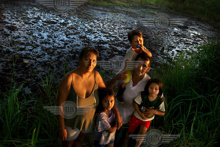 Marcos Jimenez, his wife, and his children, Karen (6), Stiven (3), and Jibran (3), stand in front of a pool of waste left by Texaco at well Shushufindi 61. The pool is on his property. Petro Ecuador has offered to clean the pool but he will not sign the authorization because he wants to be compensated with money for the damage that has been done.  Texaco left 916 open pools of waste, many of which are still abandoned. A class action lawsuit was brought against US multinational oil giant Texaco (acquired by Chevron in 2001) by more than 30,000 Ecuadorians. The case has been in the Ecuadorian courts since 2003 and relates to the dumping of billions of gallons of toxic materials into unlined pits and Amazonian rivers. In February 2011 the court ruled that Chevron should pay a fine totalling 9.5 billion USD. However, Chevron has stated that the ruling is 'illegitimate and unenforceable' and has started numerous counter proceedings in US courts. There is some doubt as to whether it will be possible to force Texaco to pay the fine.